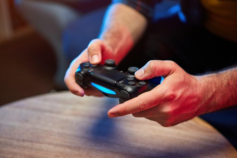 mãos mexendo em um controle remoto de videogame