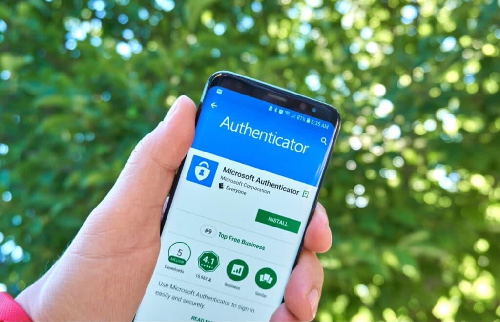 Pessoa segura smartphone exibindo página de download do Microsoft Authenticator na Play Store