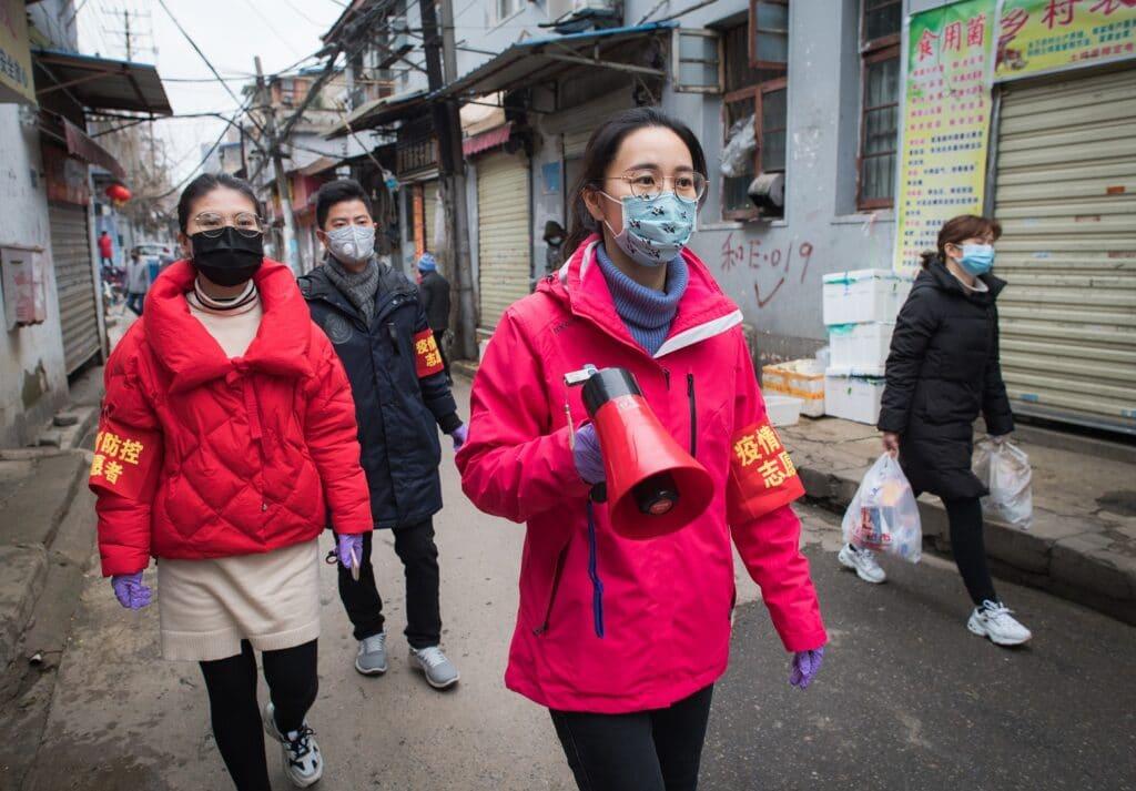 Trabalhadores comunitários usam um alto-falante para divulgar as informações sobre prevenção e controle do novo coronavírus em uma rua em Wuhan, província de Hubei, China, em fevereiro de 2020.