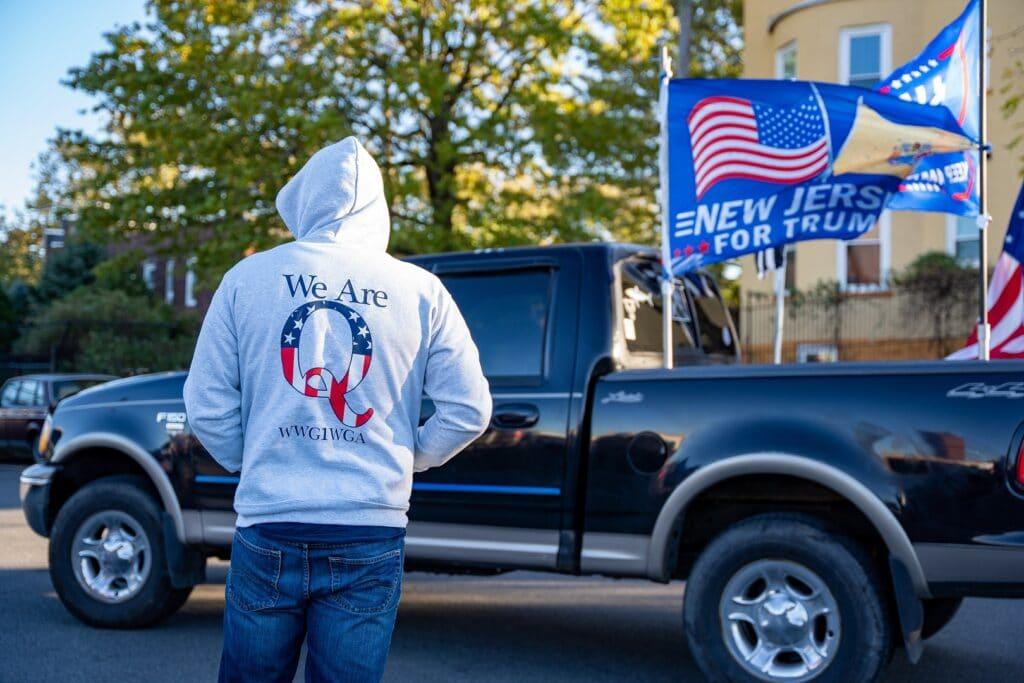 Homem encapuzado vestindo um moletom Qanon em uum comício de Donald Trump com um caminhão e bandeiras à sua frente