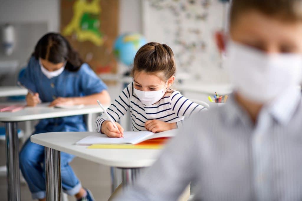 Imagem mostra criança em uma sala de aula, usando uma máscara de proteção contra a Covid-19.