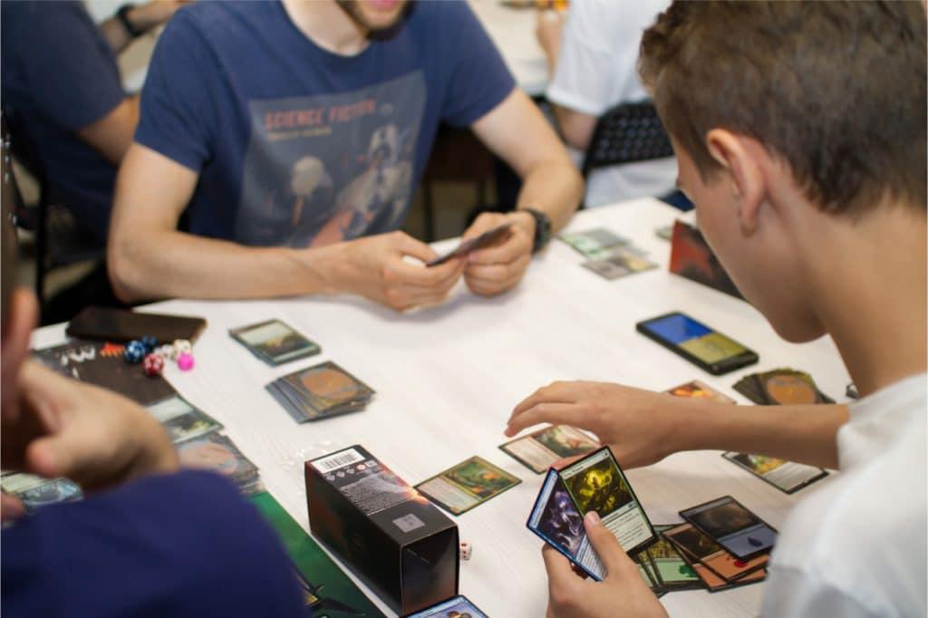 """Fãs jogando uma partida de """"Magic: The Gathering"""", da Hasbro, em uma convenção. Jogo de cartas e tabuleiro terá crossover com """"O Senhor dos Anéis"""". Imagem: Ivan Krivenko/Shutterstock"""